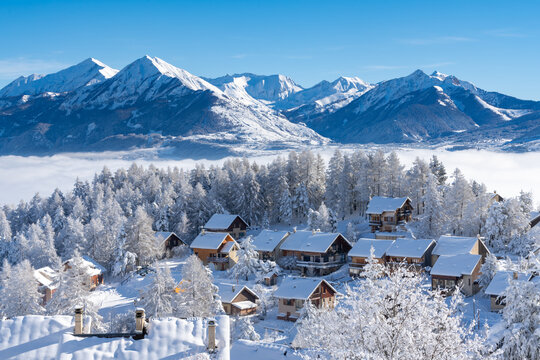 Fresh snow covers roofs and trees of Laye winter ski resort in Champsaur, French Alps. Hautes-Alpes, France
