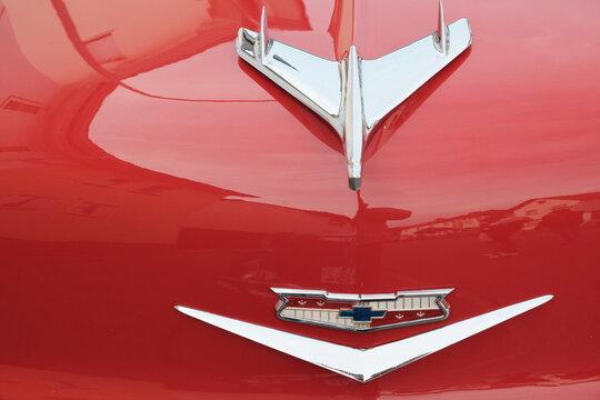 Verchromte Kühlerfigur und Markenzeichen mit Emblem eines roten Chevrolet Bel Air am 26.07.2019 bei den Golden Oldies in Wettenberg Krofdorf-Gleiberg bei Gießen in Hessen
