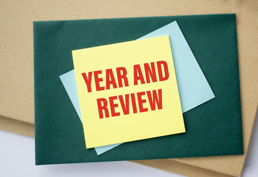 Stack of memo notes written with Year End Review on a green square background.