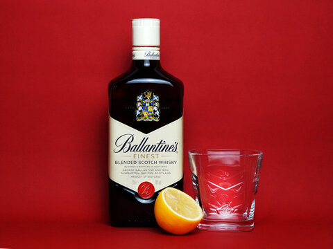 Ballantine's scotch whiskey bottle, glass and half lemon on red background