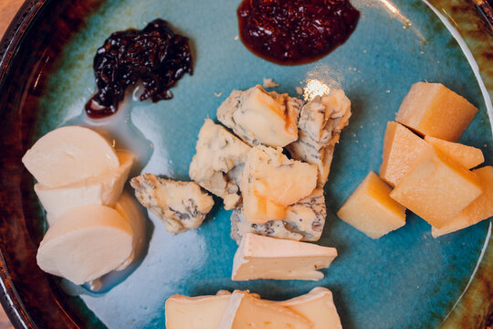Cheese plate with different kinds of cheese with thyme herbs and walnuts.