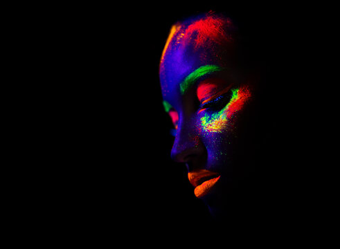trendy neon makeup on the model. Woman with ultraviolet make-up. Disco night club chameleon. UV colors. Fashion of the future bright appearance. face Art. Copy space for text background