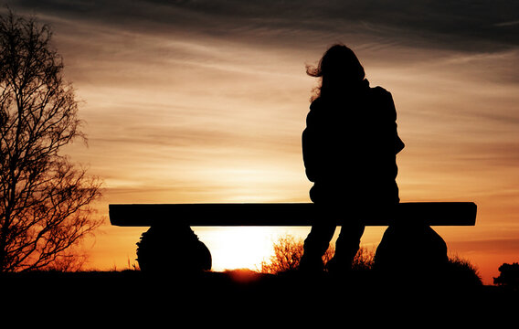 Silhouette of a woman sitting on a bench while the sun is rising