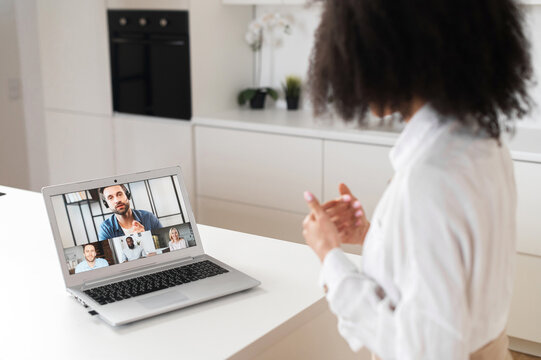 African American female businesswoman using app for distance video communication, meeting online, managing business while staying at home during covid-19, looking at laptop screen with people profiles