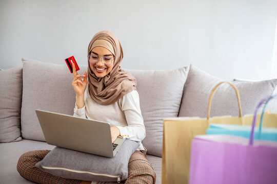 Arab woman making online purchase on laptop. Happy woman purchasing product via online shopping, using credit card. Muslim woman online shopping. I've got money to blow!