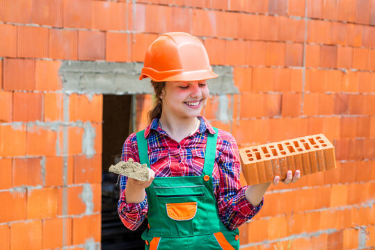 exploring tools. future engineer. happy kid use brick for renovation repairing. building construction site. child architect worker. labor day concept. childhood development. teenager girl assistant