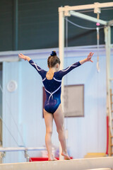A young girl in sportswear performs an exercise on a balance beam. Rhythmic gymnastics, training in the hall.