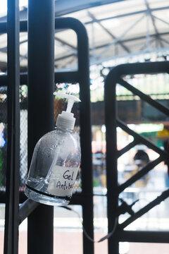 Un tarro de gel antibacterial con una etiqueta que lleva su nombre a mano, pegada a un tubo de un restaurante