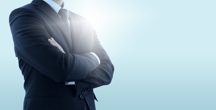 Confident business manager with crossed arms. Pale blue background with backlit.
