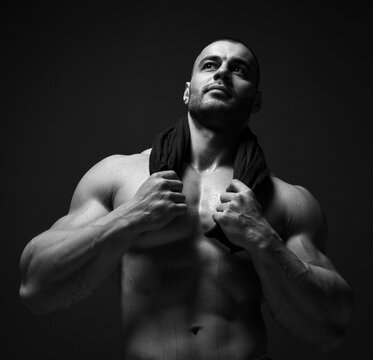 Black and white portrait muscular man, athlete, sportsman, powerlifter, bodybuilder standing with naked chest holding shirt around his neck and looks up at copy space on dark background