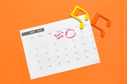 Calendar with marked date of April Fool's Day and note signs on color background