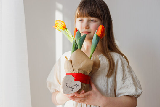 Portrait of a Caucasian girl with dark hair with a pot of tulips in her hands. Congratulations on the holiday of mothers and women. Spring. Copy space