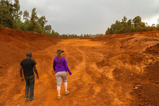 Two people walk through red dirt road