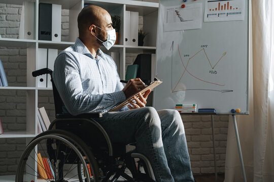 Disabled young man making presentation in office wearing medical mask