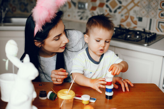Mother and son paint eggs. Family sitting in a kitchen. Preparing for Easter
