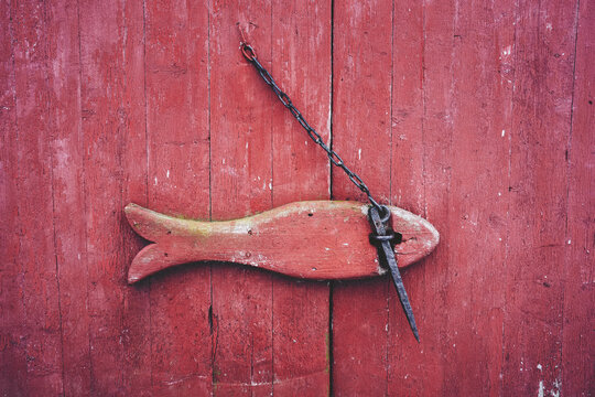 Fish formed lock on red wooden barn gate at Toten, Norway.