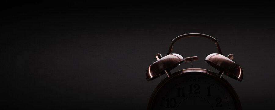 Retro alarm clock on dark background with subtle lighting