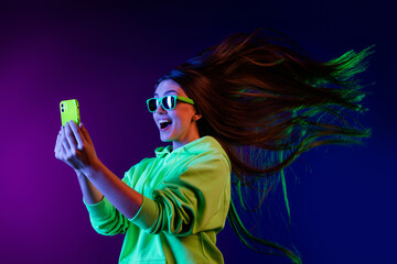 Fototapeta Photo of amazed shocked young woman look phone fast internet fly hair isolated on colorful neon background obraz