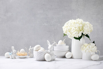 Easter decorations such as porcelain bunnies and eggs on a kitchen countertop