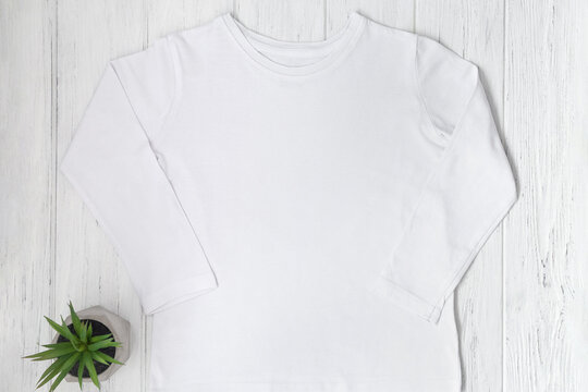 White long sleeve tshirt mockup with succulents on wooden table background. Template, flat lay