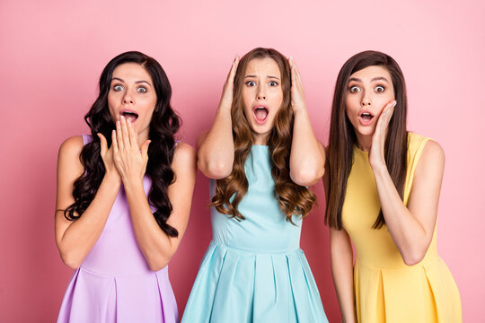 Portrait of three attractive worried girlfriends wearing dress sudden news reacion isolated over pink pastel color background
