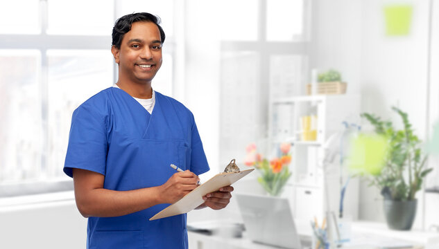 healthcare, profession and medicine concept - happy smiling indian doctor or male nurse in blue uniform writing report on clipboard over medical office at hospital background