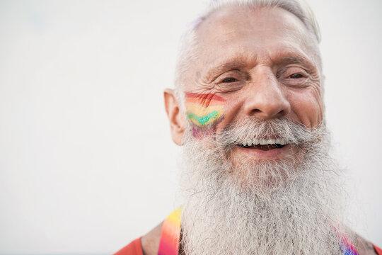 Senior gay man smiling during lgbt pride protest - Focus on face