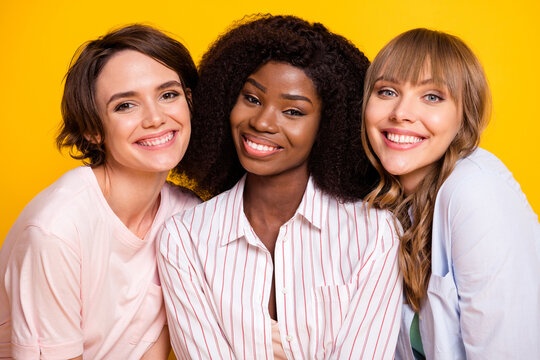 Photo of three gorgeous satisfied ladies diversity toothy smile look camera isolated on yellow color background