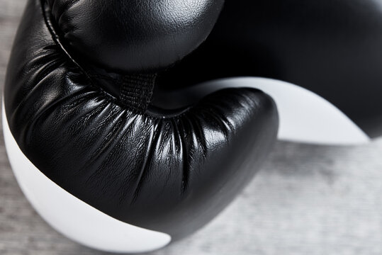 Pair of black boxing gloves on white background, closeup
