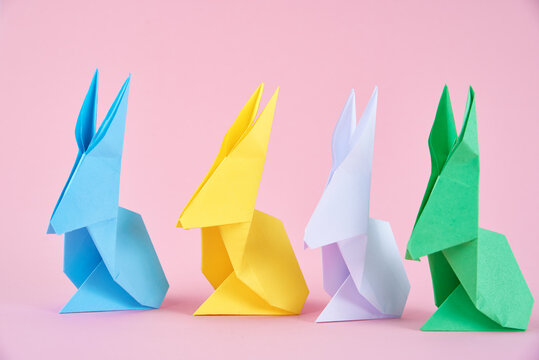 Paper colorful origami Esater rabbits on a pink background. Easter celebration concept
