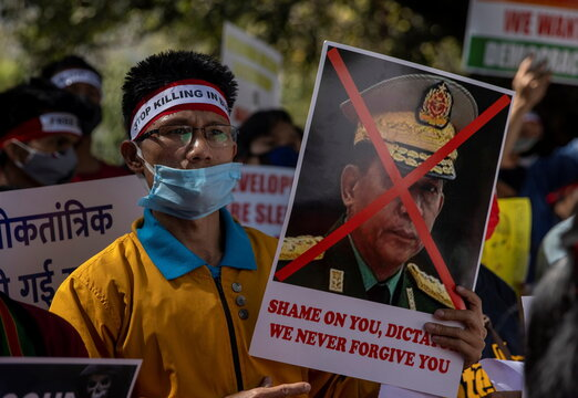 A Myanmar citizen living in India holds a poster of Myanmar's army chief Senior General Min Aung Hlaing with his face crossed out during a protest against the military coup in Myanmar, in New Delhi