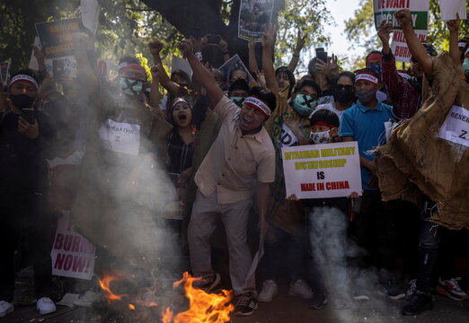 Myanmar citizens living in India shout slogans as they burn a poster of Myanmar's army chief Senior General Min Aung Hlaing during a protest against the military coup in Myanmar, in New Delhi