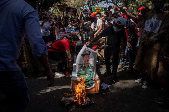 Myanmar citizens living in India burn a poster of Myanmar's army chief Senior General Min Aung Hlaing during a protest, organised by Chin Refugee Committee, against the military coup in Myanmar, in New Delhi