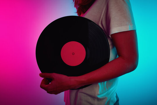 Woman hold retro vinyl disc with neon light