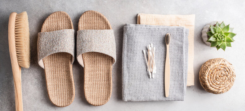 Eco spa and beauty healthcare bathroom accessories on grey stone background. Bamboo slippers, anti cellulite brush, towels, coal toothbrush, bamboo ear sticks and cotton towels