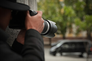 Private detective with modern camera spying on city street, closeup - fototapety na wymiar