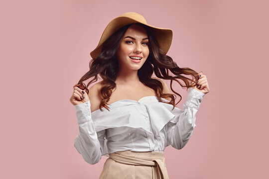 Glamour studio portrait of flirting young caucasian woman with a charming smile holding her brunette hair, wearing in stylish beige hat and fashiobable white shirt posing over pink isolated.
