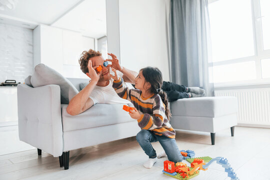 Single father with his daughter is at home together at daytime. Playing with toys