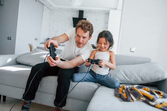 Single father with his daughter is at home together at daytime. Playing video game