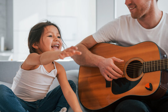Single father with his daughter is at home together at daytime. Playing guitar