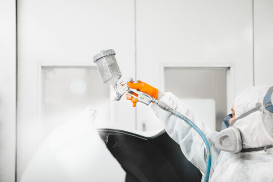 Car painter spraying white paint with spray gun on vehicle in paint chamber.