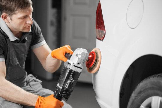 Car polishing in auto repair shop, close-up image.