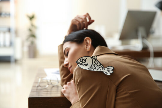 Man sticking paper fish to colleague's back while she sleeping in office, closeup. Funny joke