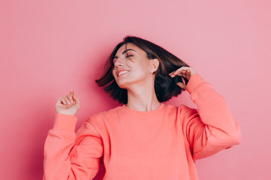 Funny young woman 20s in casual clothes isolated on pink background studio portrait. People emotions lifestyle concept. Mock up copy space. Shaking head with flowing hair