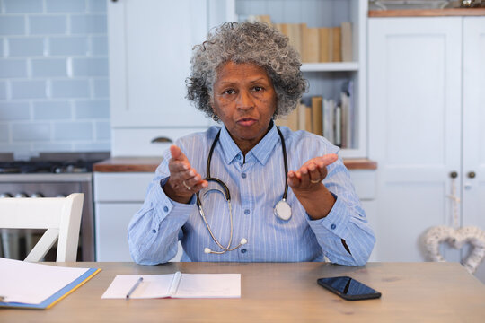 Portrait of african american senior female doctor talking looking at the camera at home