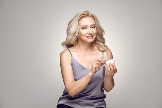 Mature adult blonde woman applies moisturizer face cream while holding a can of cosmetic product while looking at the camera on a grey isolated.