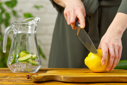 Woman cutting lemon in kitchen, lemon water, Refreshing Water with lime and lemon, healthy eating concept