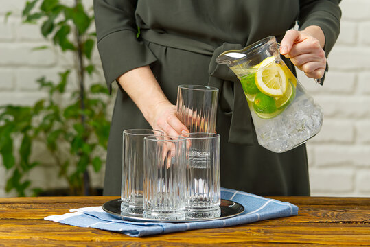 woman pouring fruit infused water from glass jag to glass, drinks, diet, detox concept
