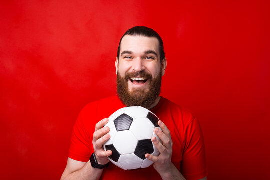 Smiling young bearded man standing over red background and holding soccer ball