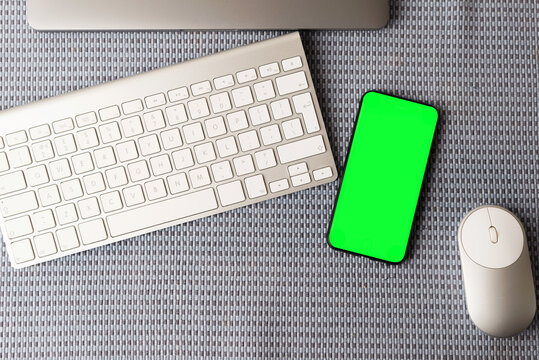 Top view photo of smartphone with green screen on desk background